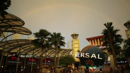 pace : Singapore - May 2, 2018: rainbow after a thunderstorm in Sentosa at sunset. Universal Studios moving globe in Bull Ring square on background. Universal Studios first Hollywood movie theme park in Asia