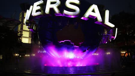 famous pace : Singapore - May 2, 2018: Universal Studios with luminous globe in Sentosa island at night with pink and green lights. Universal Studios Singapore is southeast Asias first Hollywood movie theme park.