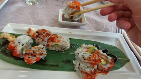took : SLOW MOTION: hand feeding on uramaki of shrimp tempura, cheese, avocado and tobiko caviar dipping in soy sauce bowl. Japanese fusion food, Asian cultures. Healthy food, light diet concept.
