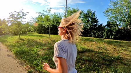 pažba : SLOW MOTION young blonde woman jogging against the sun in slow motion. A fit girl runs on a city park path, backside view. Dostupné videozáznamy