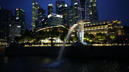 cbd : Singapore - April 27, 2018: Merlion Statue in Merlion Park with Central Business District or CBD Buildings illuminated in Marina Bay Harbor and waterfront. Scenic Singapore icon at blue hour. Stock Footage