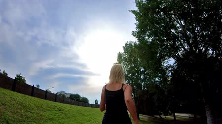pažba : SLOW MOTION tilt-shift of a blonde sporty girl running in the park at sunset for training outdoor. Leggings and gym shoes dress. backside view.