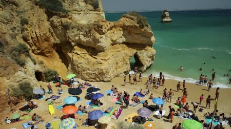 ponta da piedade : Lagos, Portugal - August 21, 2017: many people sunbathing and enjoying under colorful umbrellas on popular Praia do Camilo beach near Ponta da Piedade. Summer holidays in Algarve Coast, Portugal.