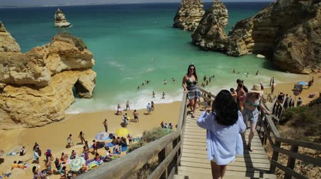 ponta da piedade : Lagos, Portugal - August 21, 2017: crowd of people sunbathing and enjoying under colorful umbrellas in popular Praia do Camilo near Ponta da Piedade. Summer holidays in Algarve Coast, Portugal, Europe Stock Footage