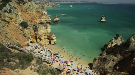 oszlopsor : Aerial view of Praia do Camilo with long steps in Algarve, Portugal, Europe. Turquoise and clear waters between rock formations and pillars of Lagos Bay. Summer holidays, Atlantic Ocean.