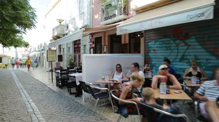 мощеный : Lagos, Portugal - August 19, 2017: restaurants and shops in the historic center of Lagos, an old sea resort on the Algarve coast. Summer season. Urban cityscape. Lagos is popular holiday destination.