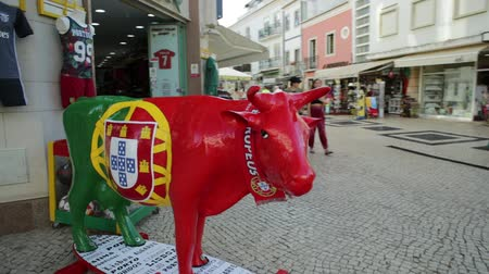 ágil : portuguese bull mascotte with Portugal flag texture. Sport shop in the historic center of Lagos, Praca de Gil Eanes. Summer season. Urban cityscape.
