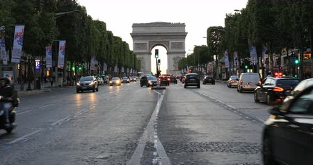 triumphal arch : Paris, France - July 2, 2017: perspective view of Champs Elysees with Arc de Triomphe in the distance in a orange sunset sky with road traffic. The arch of Triumph is a famous landmark in Paris. Stock Footage