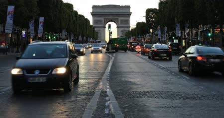 triumphal arch : Paris, France - July 2, 2017: Avenue des Champs Elysees and iconic Arc de Triomphe at twilight with traffic street. Arch of Triumph in a colorful sunset sky. Stock Footage