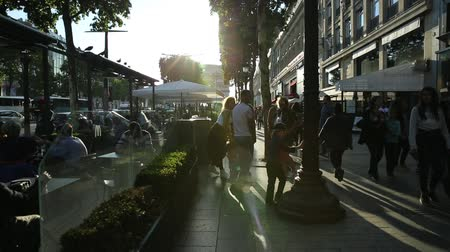 arch of triumph : Paris, France - July 2, 2017: hyper lapse of tourists walking on the most famous avenue of Paris, the Champs Elysees, for shopping in luxury shops. Lifestyle people sitting at Cafe George V.