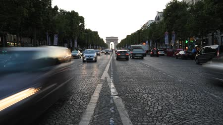 triumphal arch : Paris, France - July 2, 2017: time lapse of the cars on the Champs Elysees with the iconic Arc de Triomphe in the distance at twilight. Arch of Triumph in a colorful sunset sky.