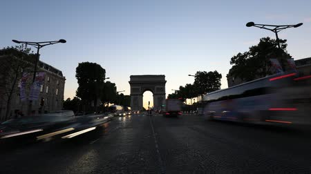 triumphal arch : Paris, France - July 2, 2017: TIMELAPSE in Champs Elysees street and center of Place Charles de Gaulle with Arch of triumph at twilight with traffic street. Arc de Triomphe at blue hour in Paris.