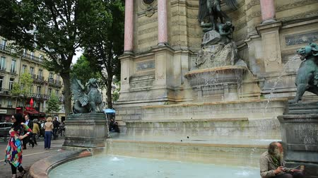 st michael the archangel : Paris, France - July 1, 2017: clochard and tourists in Place Saint-Michel and monumental Fontaine Saint-Michel with two water-spouting dragons. Historic urban landmark in Paris capital.