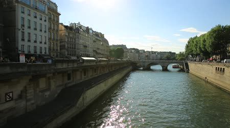 parisli : Paris, France - July 1, 2017: Pont Saint Michel bridge over river Seine, historic Parisian building within Palais de Justice complex, Ile de la Cite.Castle in former Royal Palace and Paris prison. Stok Video