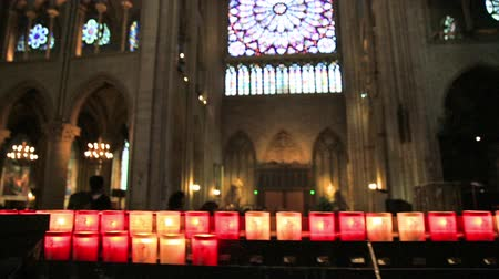 stained glass : PARIS, FRANCE - JULY 1, 2017: lighting candles in central nave altar of Notre Dame of Paris gothic cathedral. Stained glass rose windows on top. Stock Footage