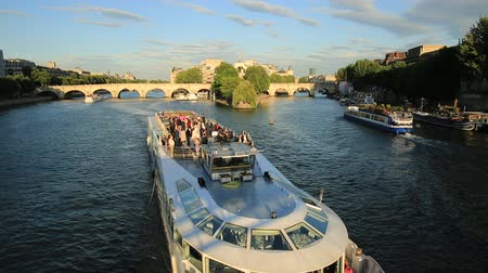 neuf : Paris, France - July 1, 2017: Tourist cruise on Seine river. Bateau mouche from Pont Neuf bridge and Notre Dame church on background. Aerial view of touristic cruise from the Pont des Arts at sunset. Stock Footage