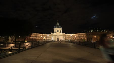 pont : Paris, France - July 1, 2017: hyper-lapse walk on Pont des Arts bridge to Institut de France building, a French learned society group of five academies. Crossing bridge POV with people in Paris night.