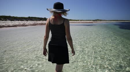 hangover : back side of woman walking in the sea water of pristine and white sand in Hangover Bay, Nambung National Park, Western Australia. Blonde girl happiness walk. Copy Space.