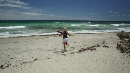 australian landscape : Happy woman running on white beach waving Australian Flag. Blonde tourist enjoying in Mettams Pool, North Beach near Perth in Western Australia. Sunny day, Blue sky. Beach freedom summer holiday. Stock Footage
