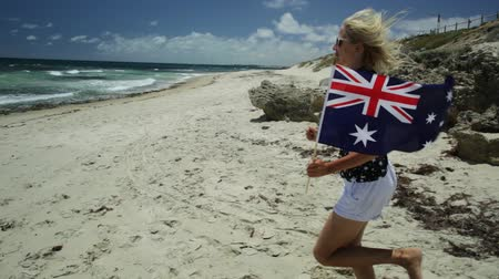 australian landscape : close up of woman running on white beach waving Australian Flag. Blonde tourist enjoying in Mettams Pool, North Beach near Perth in Western Australia. Sunny day, Blue sky. Beach freedom summer holiday