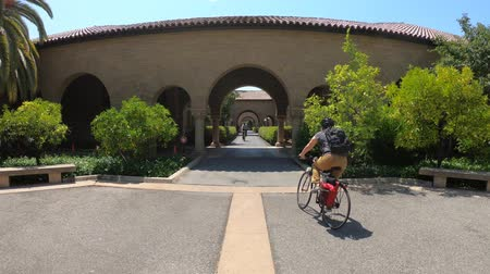 колледж : Palo Alto, California, United States - August 13, 2018: Main Quad archway at Stanford University Campus in Silicon Valley with students moving by bicycle.
