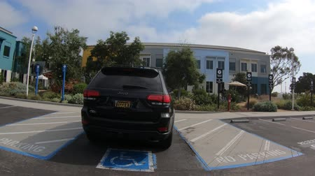 parkoló : Menlo Park, California, United States - August 13, 2018: Numbered seats for employees car in front of the colorful buildings of Facebook Headquarters Campus in Silicon Valley, San Francisco bay area.