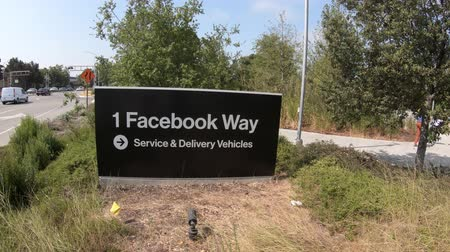 silicon : Menlo Park, California, United States - August 13, 2018: Facebook HQ entrance sign on new campus in Silicon Valley. On background a young employee goes to work by the company bicycle.