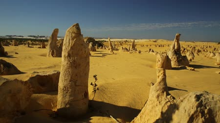 západ : Ground POV hyper lapse in the Pinnacle limestone formation of desert of the Pinnacles in Nambung National Park in Western Australia. Cinematic speed flight over a desert or an alien planet background.
