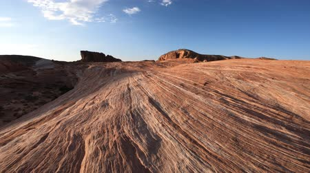 valley of fire : POV walking on Mojave desert Valley of Fire State Park, Nevada, United States. Stripes in red rock along the Fire Wave Hike at sunset light. Gibraltar rock on background.