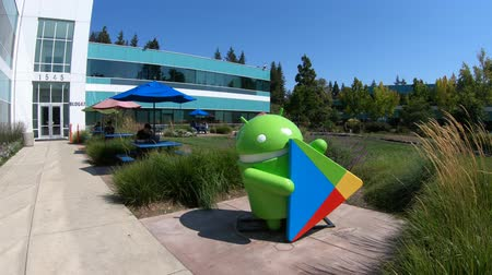 штаб квартира : Mountain View, California, United States - August 13, 2018: Google Play Android Nougat statue at Charleston Campus of Google Headquarters in Silicon Valley near Googleplex. Building 47. Стоковые видеозаписи