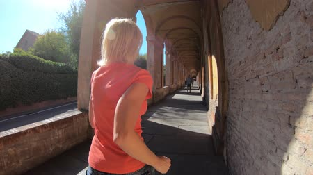 madona : A sportwear woman running under San Lucas portico: the longest porch in the world leading to the San Luca Sanctuary on Colle della Guardia. Bologna city of Italy.