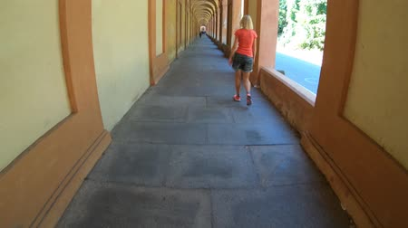 madona : italian woman walking under San Lucas longest archway in the world leading to the San Luca Sanctuary of Bologna city in Italy. Dostupné videozáznamy