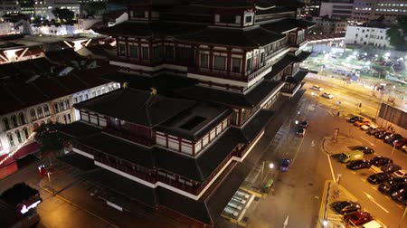 relics : tilt PANORAMA of Buddha Tooth Relic Temple of Singapore from top view, Southeast Asia. Spectacular buddhist temple in Chinatown district with business district skyline by night.