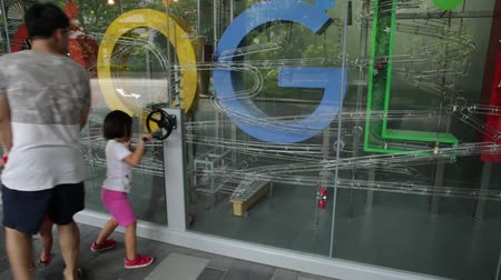 singapur : Singapore - May 5, 2018: Google Sign on lobby of new Google Headquarters, Mapletree Business City II in Singapore, Asia. Little girl turning the funny wheel that chimes. Stok Video