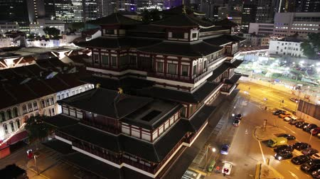 relics : Buddha Tooth Relic Temple of Singapore from aerial view, Southeast Asia. Spectacular buddhist temple in Chinatown district with business district skyline on background by night.