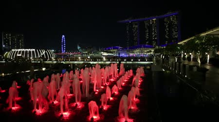 szingapúr : Singapore - April 28, 2018: scenic Fullerton Fountain near to Fullerton Bay Hotel in Clifford Square, Marina Bay walkway promenade. Marina Bay Sands during Laser lights at night. Popular free show. Stock mozgókép