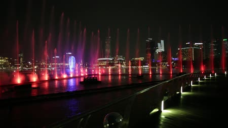 spettri : Singapore - 26 aprile 2018: panorama dal molo di fontane danzanti Spectra: Light Water Show sul lungomare di Marina Bay Sands. Grattacieli del Central Business District su sfondo. Filmati Stock