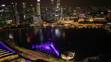 skypark : Singapore - April 26, 2018: Aerial time lapse of Singapore marina with financial district skyscrapers at night in the harbor. Rooftop above Singapore skyline. Night laser show. Stock Footage