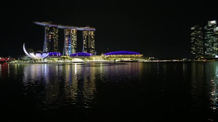 odráží : Singapore - April 28, 2018: Singapore downtown skyline with skyscrapers of Business District from pedestrian bridge in marina bay promenade. Singapore with the lights of night reflecting in the bay.