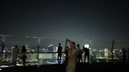 skypark : Singapore - May 3, 2018: people sitting on terrace ejoying panoramic views from Observation Deck Skypark of Marina Bay Sands hotel and casino. Financial district skyline on background by night. Stock Footage