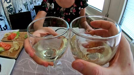 cheers : SLOW MOTION: white wine cheers with focos on hands in a Japanese sushi restaurant in slow motion. Cheers at dinner with a woman.