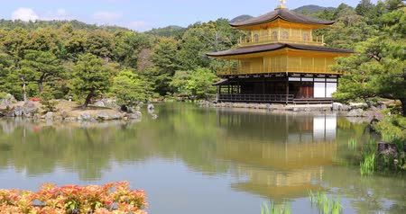 teljesen : Scenic landmark Kinkakuji or Rokuonji, Unesco site of Kyoto, reflected on lake.The Golden Pavilion, whose top two floors are completely covered in gold leaf, is a ancient Zen temple. Day light shot. Stock mozgókép