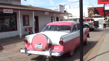 trace : Williams, Arizona, Verenigde Staten - 14 juni 2007: ARCHIEFVOET over een klassieke roze Cadillac-auto in de historische stad Williams door Route 66 in een oud benzinestation. Stockvideo