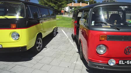 volkswagen : Cascais, Portugal - August 6, 2017: historic Volkswagen bus cars of red and yellow colors in the vintage cars show in historic Cascais town center. Stock Footage