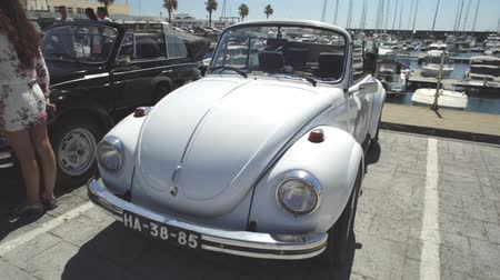 volkswagen : Cascais, Portugal - August 6, 2017: round view of a cabriolet Volkswagen Beetle car of white color during the vintage cars show in historic Cascais town center. Stock Footage