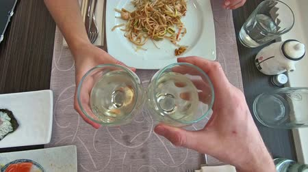 anniversary congratulations : SLOW MOTION: Aerial view of two white wine glasses doing cheers to celebrate an event in a restaurant at dinner, set table background and slow-motion effect.