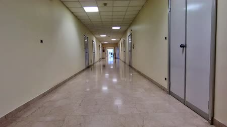 ér : Long walkway corridor with white walls of a hospital lane interior. Blurred medical and healthcare background.
