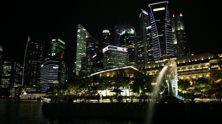 night singapore : Singapore - April 27, 2018: night scenic Singapore touristic symbol at blue hour, the Merlion Statue in Merlion Park with luminous skyline of CBD Buildings anf Fullerton Hotel in Marina Bay waterfront Stock Footage