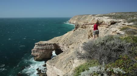 np : Happy woman with open arms at Natural Bridge in Kalbarri National Park, Western Australia. Backpacker girl on cliffs of Indian Ocean coastline. Australian Outback travel. Blue sky, summer sunny day.