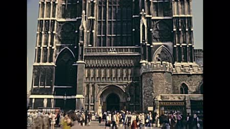historisch : LONDON, UNITED KINGDOM - CIRCA 1979: facade of Westminster Abbey church in London. Tourists in vintage dress in historic footage in 1970s.